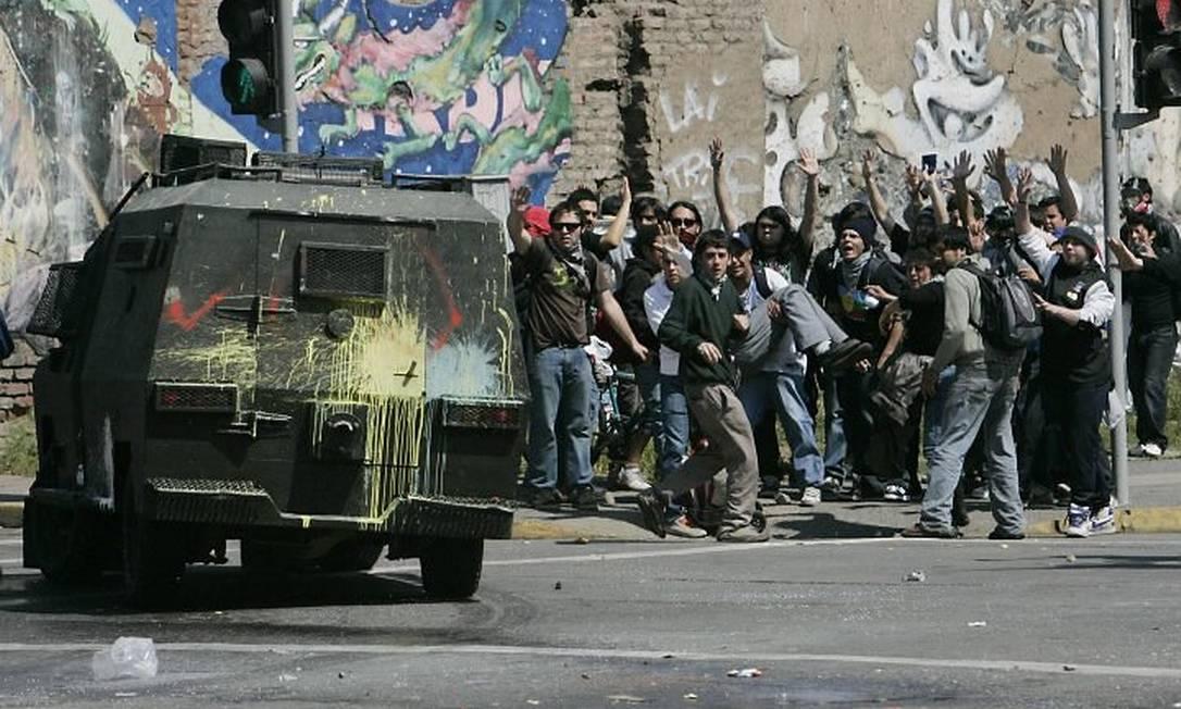 Estudantes levantam as mãos para o alto diante de um veículo policial na capital chilena, Santiago - Reuters