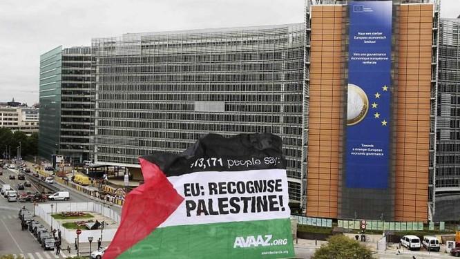Ativistas levantam bandeira palestina em frente a sede da ONU em Bruxelas - AP