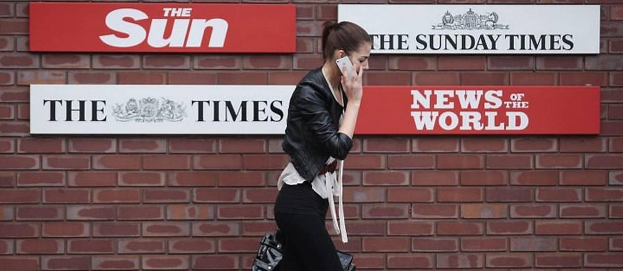 Mulher passa em frente à sede da News International - Reuters