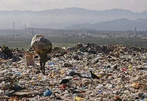 Com a Reduc, ao fundo, um homem cata recicláveis em Jardim Gramacho: multas ambientais acabam no lixo (Foto: André Teixeira Agência O Globo)