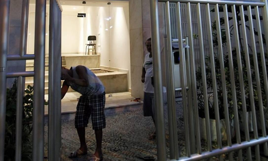 Homens consertam o portão do prédio, na Rua Joana Angélica, que foi arrombado pela dupla de assaltantes (Foto: Marcelo Carnaval Agência O Globo)