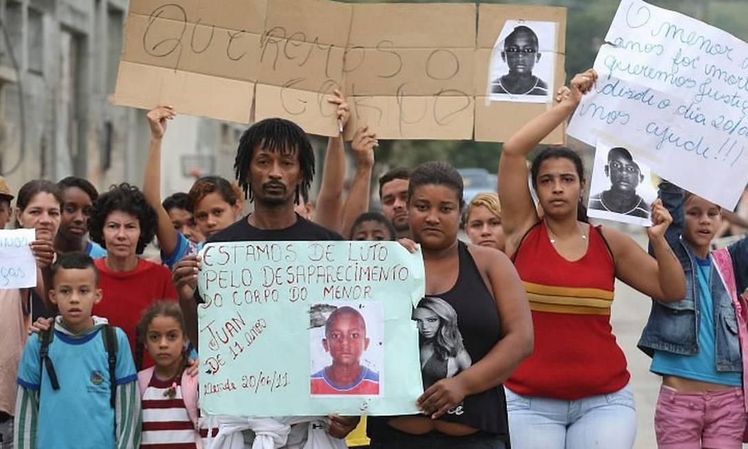 Com uma foto do filho, os pais de Juan de Moraes participam de um protesto em Nova Iguaçu, na Baixada (Foto: Cléber Júnior Extra Agência O Globo)