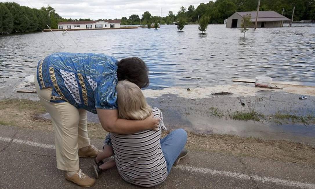 Duas mulheres observam desoladas enquanto a água do rio Mississippi invade a cidade de Vicksburg.