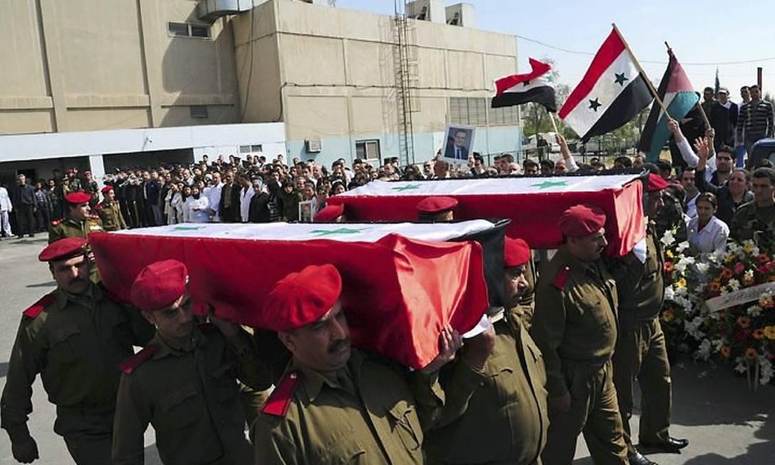 Caixões que levariam corpos de soldados e policiais mortos na segunda-feira deixam um hospital em Damasco - AP