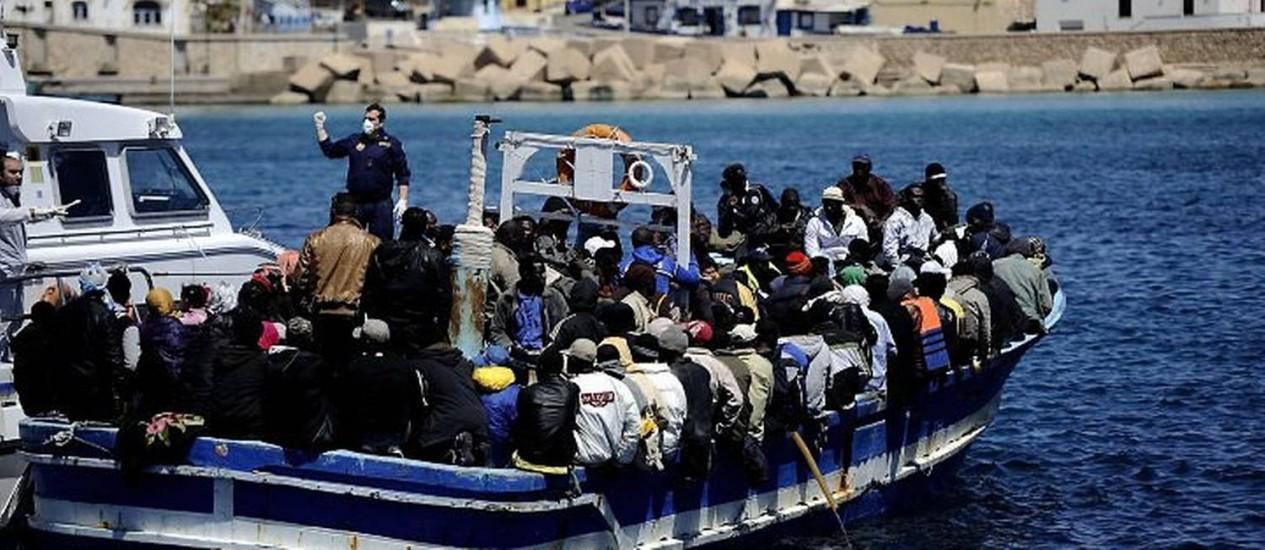 Barco com imigrantes é escoltado por policiais quando tentava chegar à ilha italiana de Lampedusa em 9 de anbril - AFP
