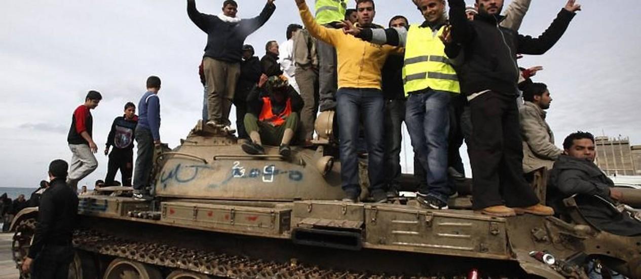 Jovens em cima de tanque protestam contra Muamar Kadafi em Benghazi, na Líbia Reuters