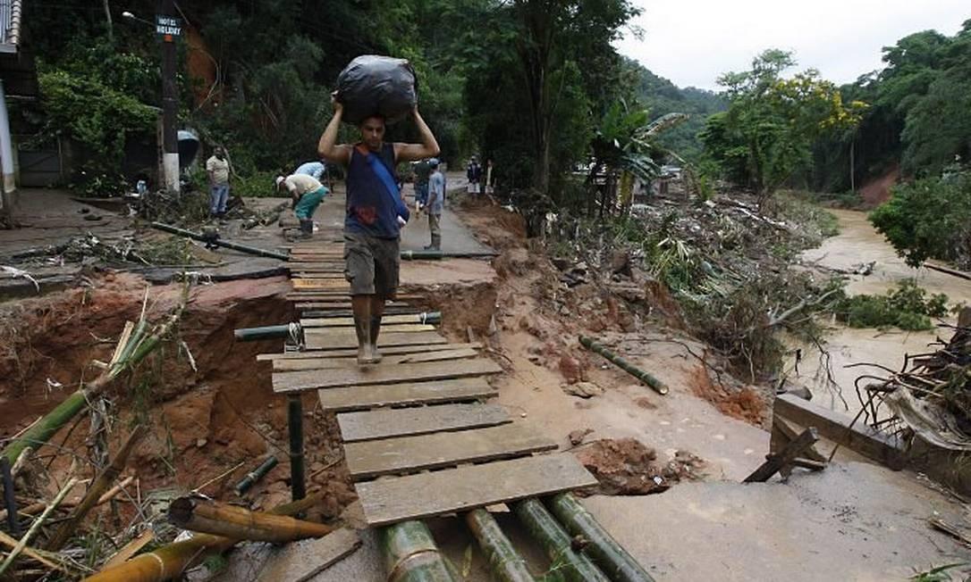 Moradores no que sobrou de uma ponte em Teresópolis Foto: Domingos Peixoto