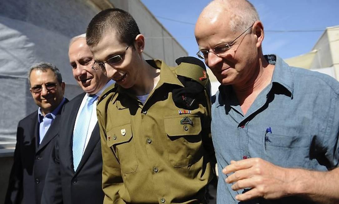 Shalit, entre o pai e o primeiro-ministro israelense, Benjamin Netanyahu, em base militar de Israel - AP