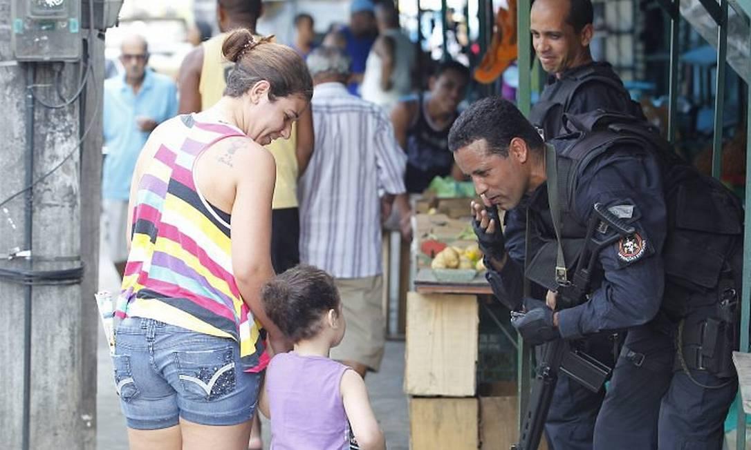 Invasão da Vila Cruzeiro na Penha. Na foto moradores recebem bem os policiais do Bope que manda um beijo para a menina que brinca (Foto: Gustavo Azeredo Extra)