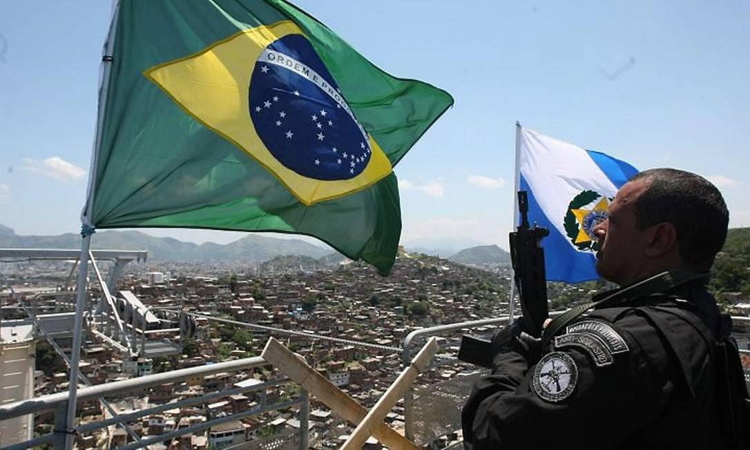 Policiais hasteiam bandeira do Brasil no alto do teleférico do Alemão. Foto: Bruno Gonzalez