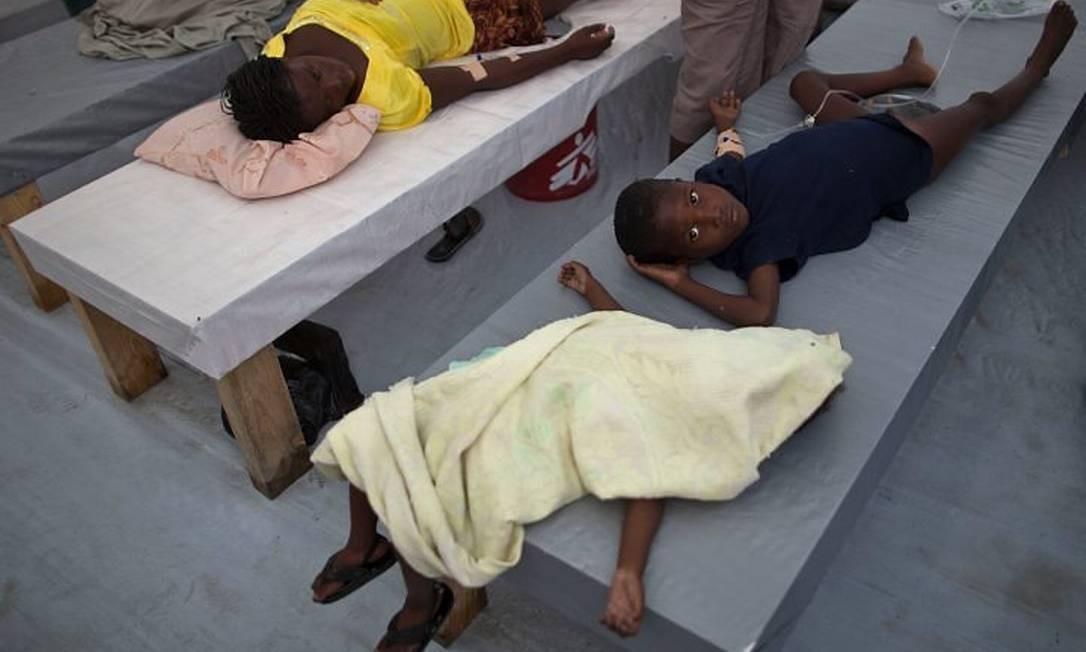 Menino recebe atendimento em hospital em Porto Príncipe ao lado do corpo de menina de 2 anos, vítima do cólera - AP