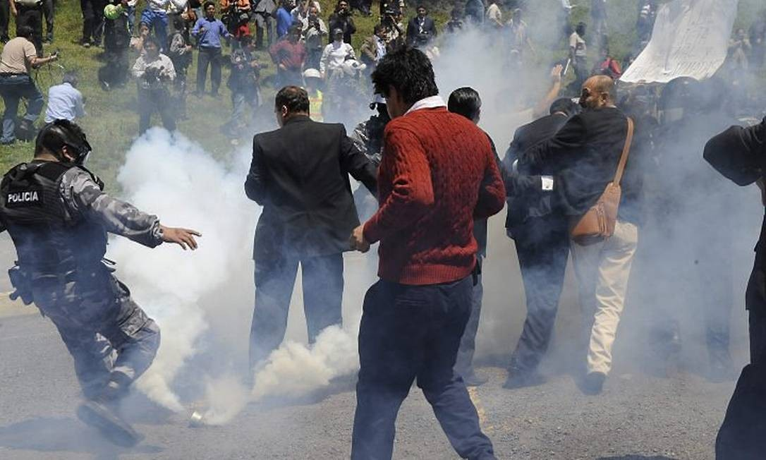 Presidente equatoriano, Rafael Correa (de terno), deixa um quartel em Quito onde discursou em meio a protestos - AFP