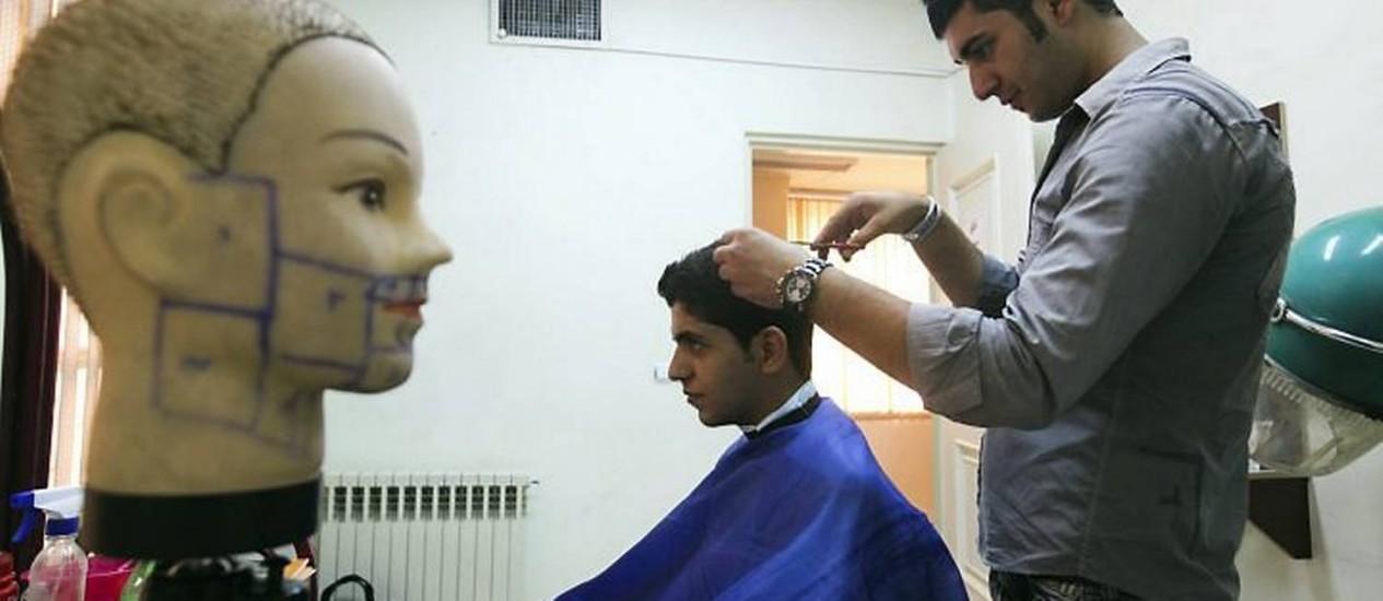 Barbeiro corta cabelo de cliente em Teerã - Reuters
