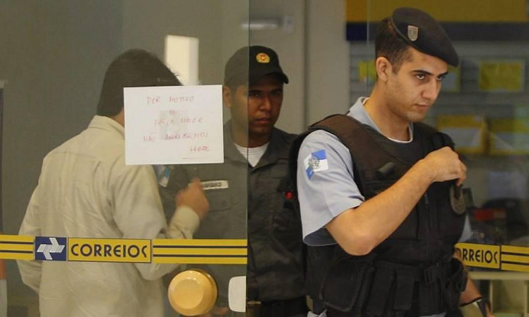 POLICIAIS MILITARES examinam a agência dos Correios após o assalto Foto de Gabriel de Paiva - O Globo