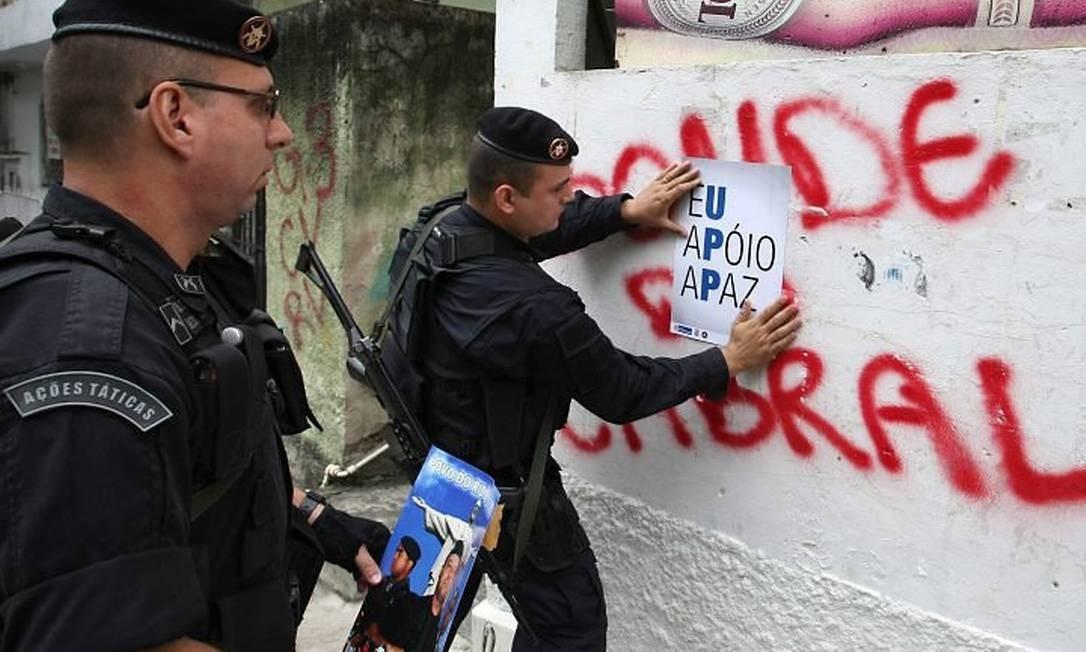 Policiais colam cartazes de boas-vindas no Morro do Andaraí. Foto de Márcia Foletto