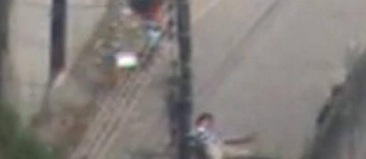 O suspeito de tráfico 'Cheiroso' estendido no chão logo após ser baleado Reprodução