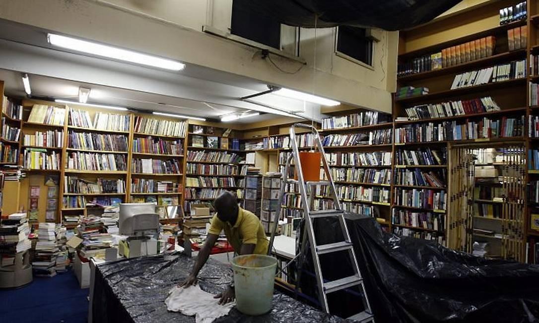 UM FUNCIONÁRIO da Leonardo da Vinci tenta secar a água suja que escorre do teto da livraria, no Centro Foto de Domingos Peixoto - O Globo