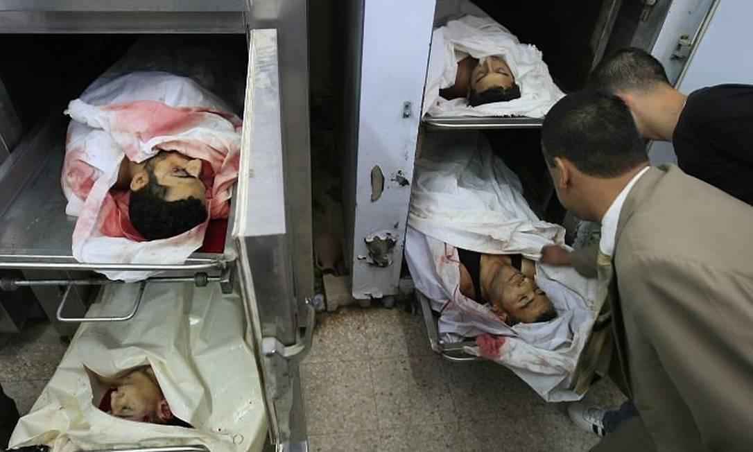 Dois homens observam os corpos dos quatro palestinos mortos no necrotério de um hospital em Deir al-Balah - AFP