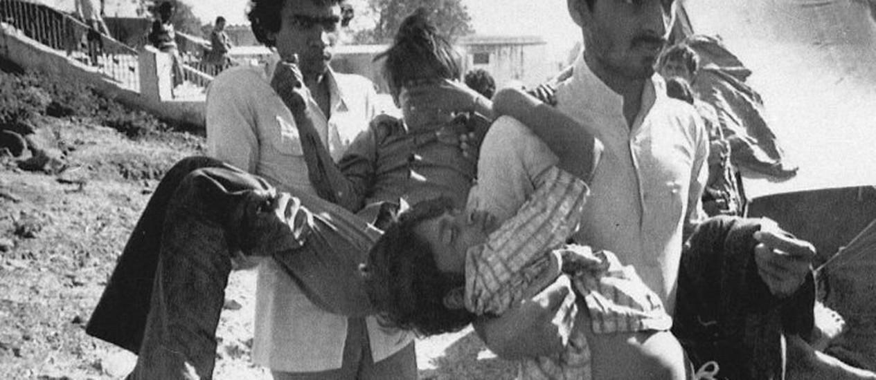 Foto de 5 de dezembro de 1984 mostra dois homens carregando crianças afetadas pelo vazamento de gás de uma fábrica da Union Carbide em Bhopal, na Índia - AP