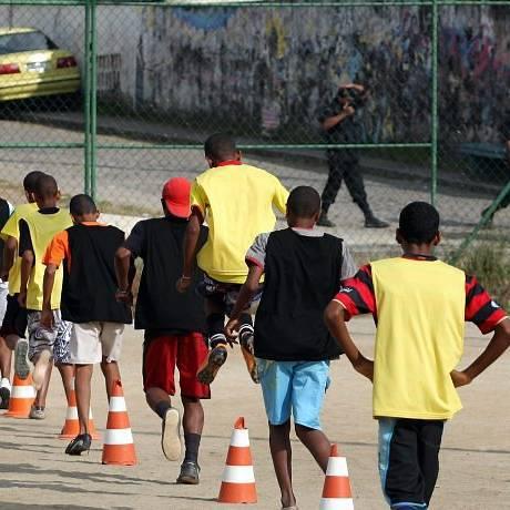 COM POLICIAIS ao fundo, meninos treinam para torneio de futebol entre as favelas Foto de Gabriel de Paiva - O Globo