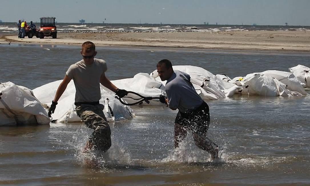 Voluntários trabalham para conter mancha de óleo que se alastra pelo Golfo do México Foto: AFP