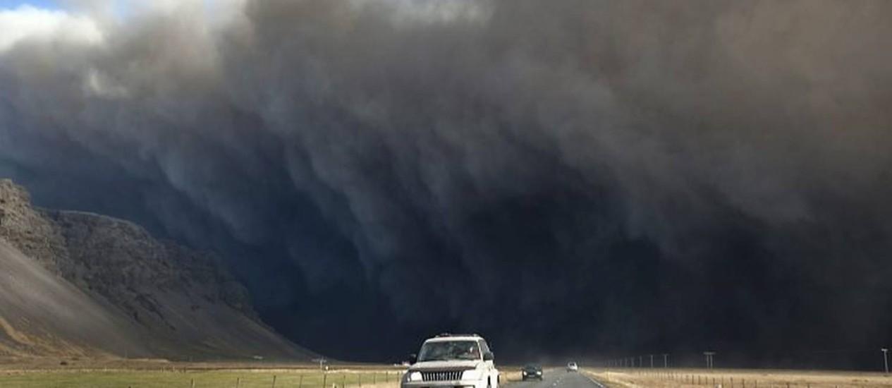 NA Islândia, um carro com cientistas deixa a região da erupção do Eyjafjallajoekull. Atrás dele, a nuvem de cinzas e detritos ejetada pelo vulcãoFoto: AFP