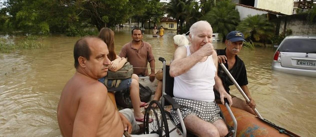EM UMA CADEIRA de rodas, Amador Gonzalez Vilhena, de 85 anos, é resgatado da enchente por vizinhos Foto de Domingos Peixoto - O Globo