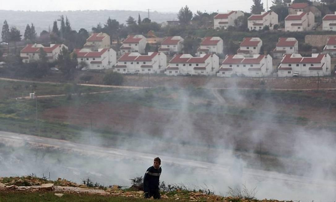 Jovem palestino cata pedras para jogar em soldados israelenses que lançavam gás lacrimogêneo durante confronto em Nabi Saleh, perto de Ramallah, devido a um protesto contra a ampliação do assentamento de Halamish, ao fundo - AFP