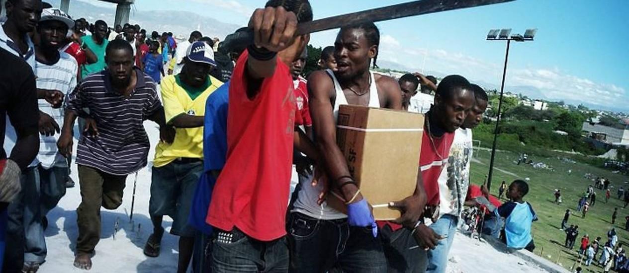 Haitianos brigam por alimentos distribuídos por um helicóptero da Marinha americana em Porto Príncipe AP
