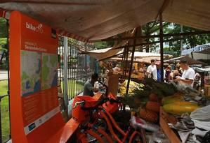 BICICLETAS E BARRACA de feira juntas: para trabalhar, feirante teve que improvisar e dividir espaço com uma das estações do Rio Bike Foto: Guilherme Leporace - O Globo