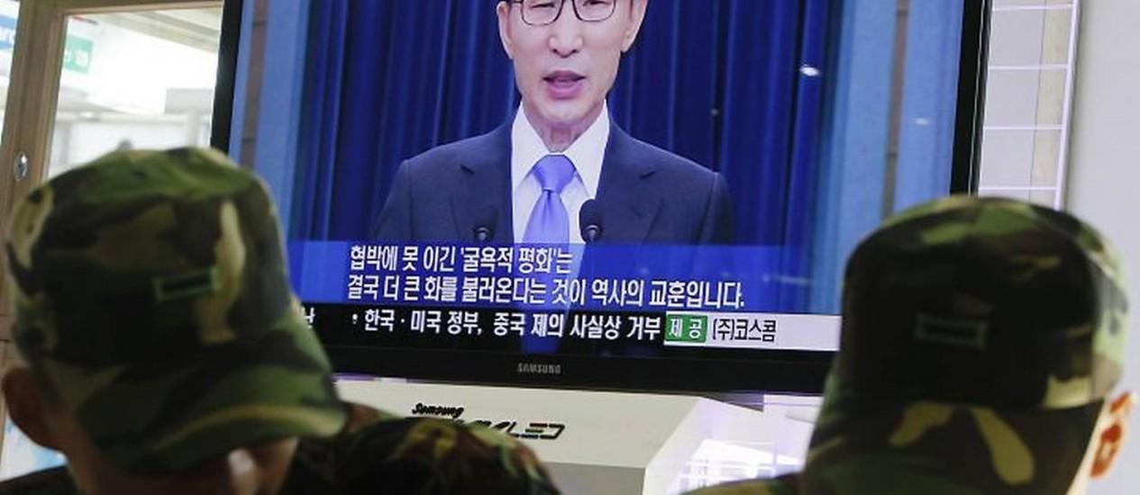 Soldados sul-coreanos conversam em frente a TV que transmite discurso do presidente - AP