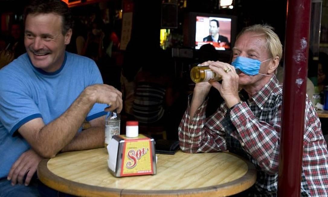 Homem usa máscara enquanto toma cerveja em bar na Cidade do México.