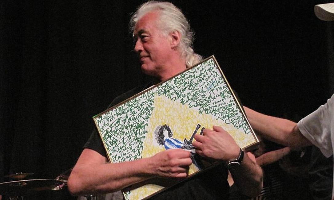 Jimmy Page com o presente que recebeu no palco, um quadro com assinaturas de fãs formando o desenho da bandeira do Brasil André Coelho
