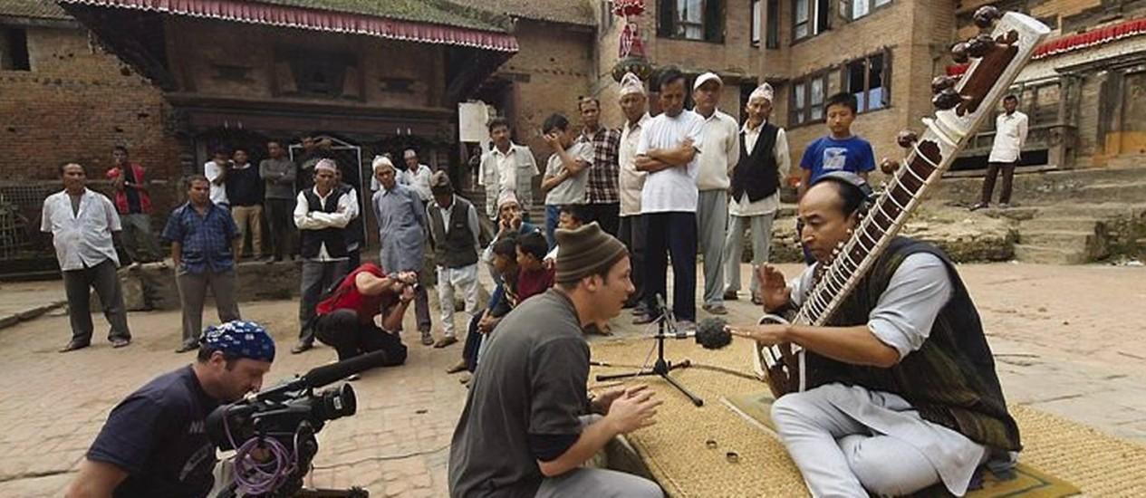 Músicos que participaram do projeto 'Playing for change', que reuniu músicos de rua do mundo inteiro. Na foto de divulgação, Mark Johnson, no Nepal, conversa com o citarista Tara Bir Tuladhar