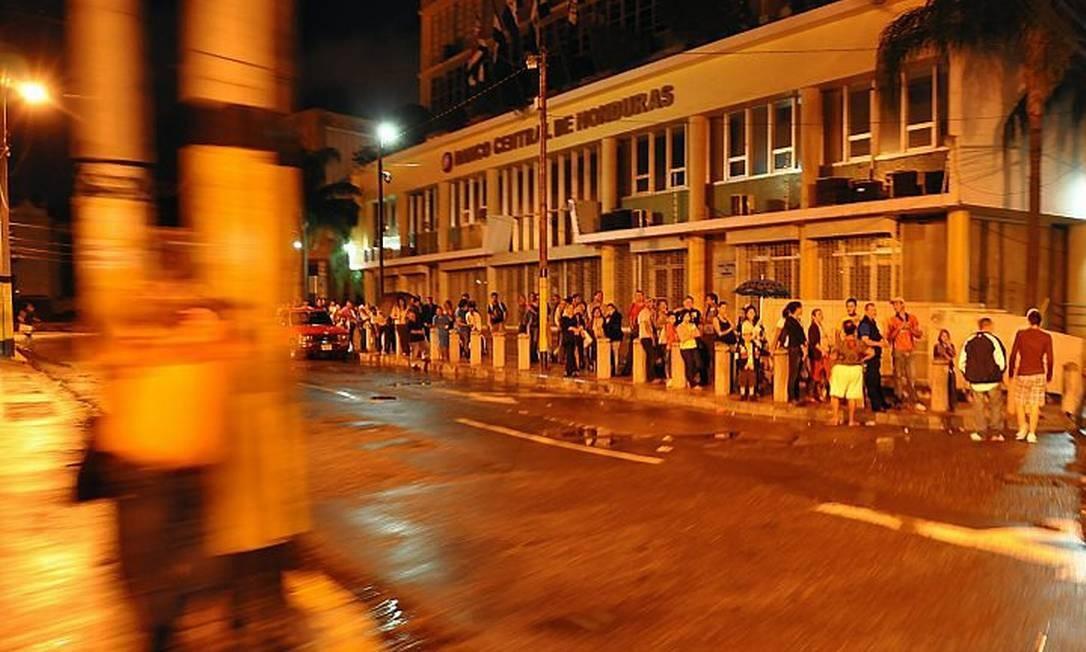 Em Honduras, moradores aguardam por transporte para ir para casa devido ao toque de recolher imposto pelo governo interino. Partidários do presidente deposto de Honduras, Manuel Zelaya, planejam uma manifestação AFP