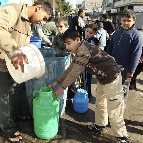 Em Gaza, palestinos enchem vasilhames com água aproveitando a interrupção dos ataques israelenses para passagem de ajuda humanitária Reuters