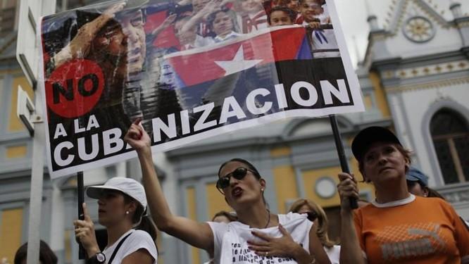 Opositores marcham com cartaz que se lê 'não à cubanização' durante protesto contra a reforma da educação na Venezuela - AP