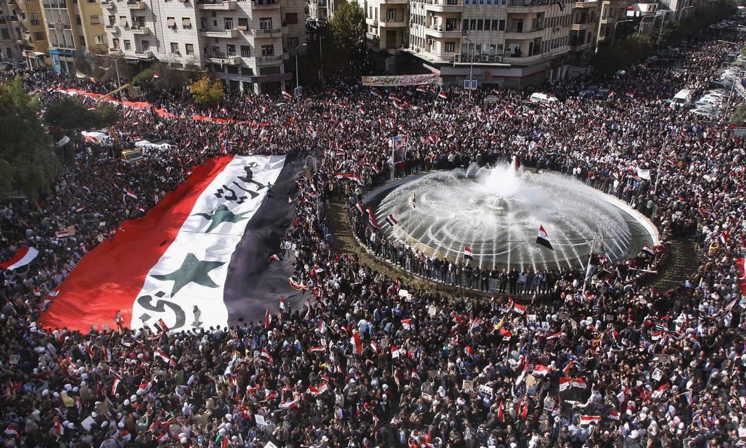 Em Damasco, milhares de pessoas saíram às ruas neste domingo: suspensão de Liga Árabe isola ainda mais regime de Assad Foto: AP