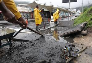 Funcionários da prefeitura começam o dia limpando os bueiros no acesso à favela da Rocinha Foto: Márcia Foletto / O Globo
