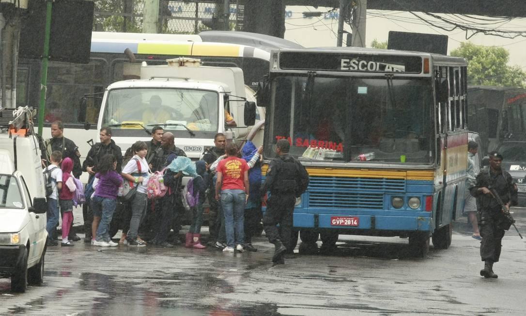 Sob a chuva e o olhar dos policiais, estudantes embarcam no ônibus escolar Foto: Fabiano Rocha / O Globo
