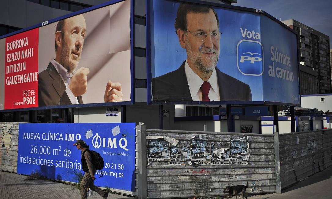 Homem passa por cartazes de Rubalcaba e Rajoy na cidade basca de Barakaldo Foto: AP