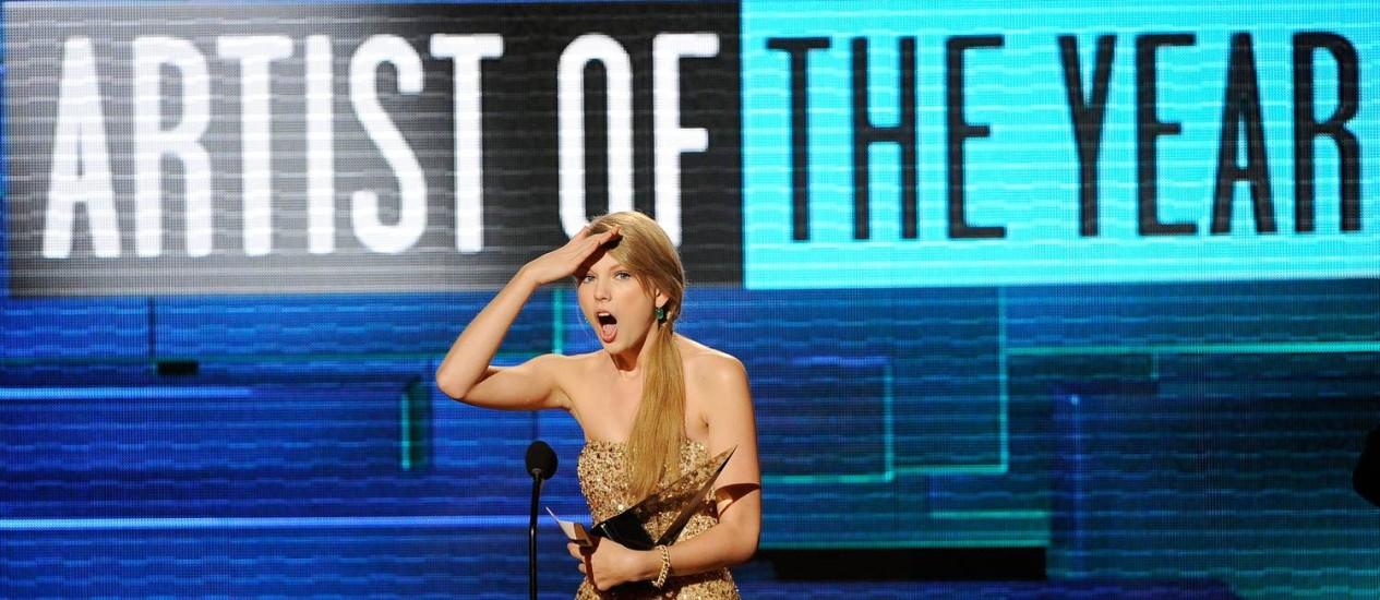 A cantora Taylor Swift recebe o prêmio de artista do ano no American Music Awards, em Los Angeles Foto: AFP