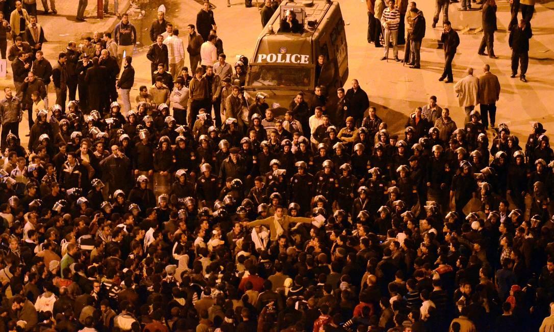Manifestantes observados pela polícia na Praça Tahrir, no Cairo Foto: AP