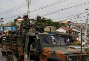 Sobre caminhão camuflado, militares do Exército que participam da ocupação reforçam a segurança nos acessos e dentro das favelas que compõem o complexo Foto: Guilherme Pinto / O Globo