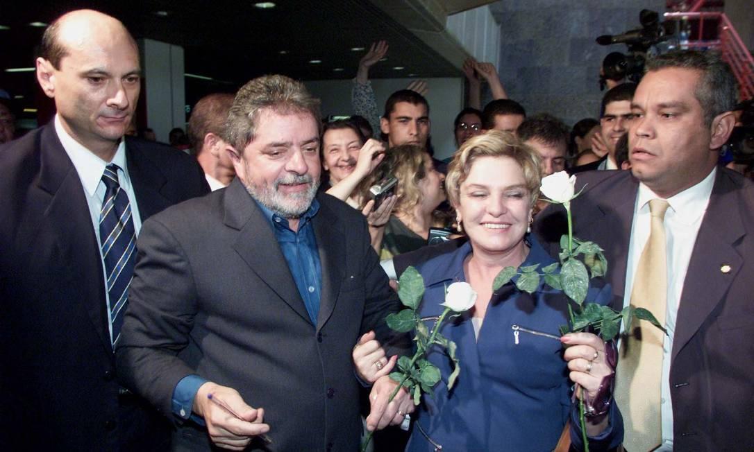 O então presidente eleito Luiz Inácio Lula da Silva e dona Marisa Letícia ganham flores brancas de simpatizante no aeroporto de Brasilia Ailton de Freitas / O Globo