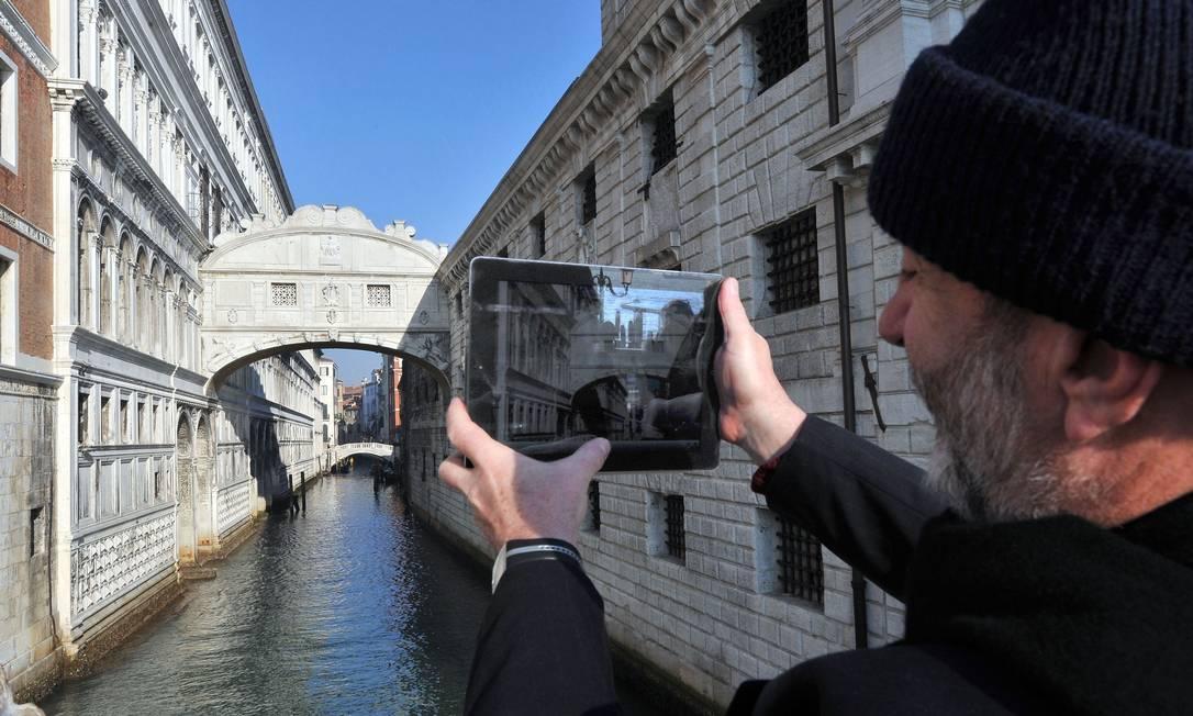 Em Veneza, turista fotografa a Ponte dos Suspiros antes da pandemia. A cidade é uma das que podem ser exploradas pelo jogo de celular Foto: ANDREA PATTARO / AFP