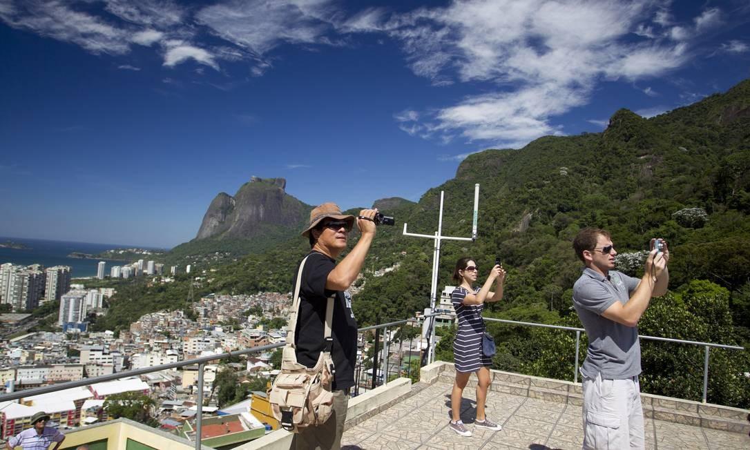 Turistas estrangeiros filmam a paisagem no entorno da Laje do Carlinhos, na entrada da Rua 1, na Rocinha Foto: Márcia Foletto / O Globo