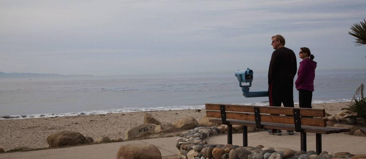 Casal observa o mar numa das praias de Santa Bárbara, na Califórnia: da orla, com telescópios públicos, frequentadores podem observar pássaros Foto: Ann Summa / The New York Times