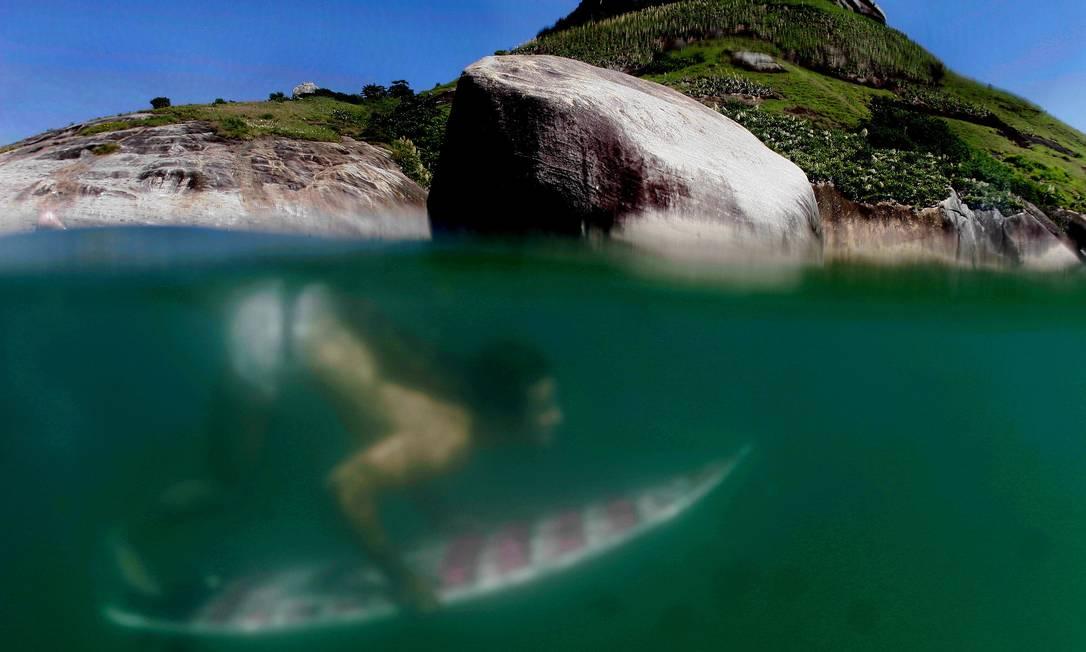 Surfista mergulha nas águas da Praia do Recreio dos Bandeirantes O Globo / Marcelo Piu