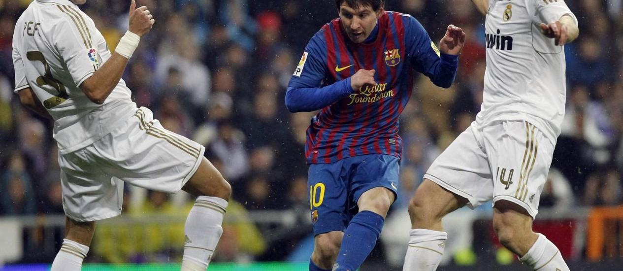 Entre Pepe e Xabi Alonso, Messi dá o passe para um companheiro no jogão entre Real Madrid e Barcelona no Santiago Bernabéu Foto: JUAN MEDINA / REUTERS